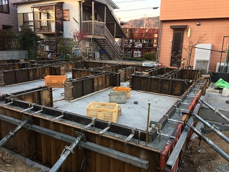 基礎工事も段階があり、最初に図面上の建物の位置を現場に落とし込み、基礎を作るための位置だしをします。これを丁張り(ちょうはり)と言います。それが終わると地面を掘って地面を整えてつき固め、湿気が上がるのを防止するシートを敷き込み鉄筋を組みます。べた基礎の場合は写真の様な膨大な鉄筋量になります。人が通り抜けるために基礎の立ち上がりの一部に開口部を設けますが、その部分は補強のためにさらに鉄筋を敷きます。地盤はしっかりしてる上にこれだけの鉄筋コンクリートの盤を作る訳ですから建物が沈む、傾く、割れるなどの心配はありません。安心です。